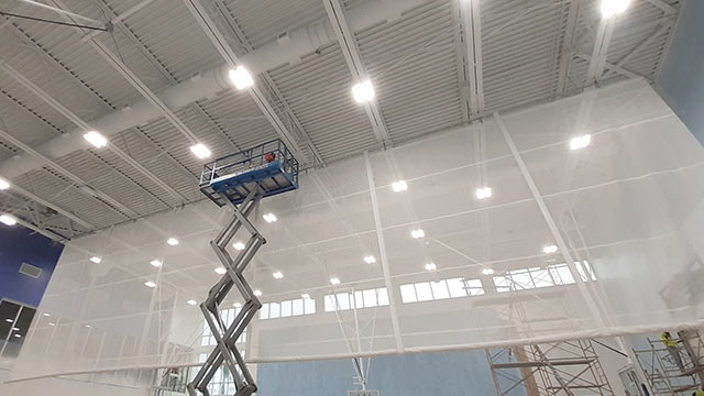 Grand Cayman interior gymnasium lift with workers insprecting joists